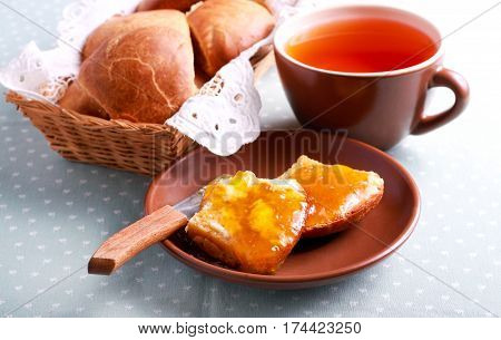 Scones with butter and marmalade and cup of tea