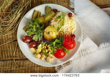 Different types of vegetables on white plate. Pickled cucumbers, tomato cherry, greens, berries, baked apples served on white plate. Coocked healthy vegetables on plate. Salad of vegetables.