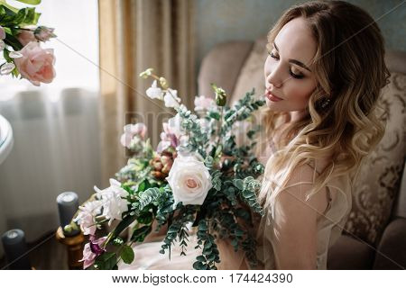 Beautiful young woman in a house dress in the boudoir decorated with beautiful flowers sitting on a white bed with a canopy fashion beauty sensuality femininity