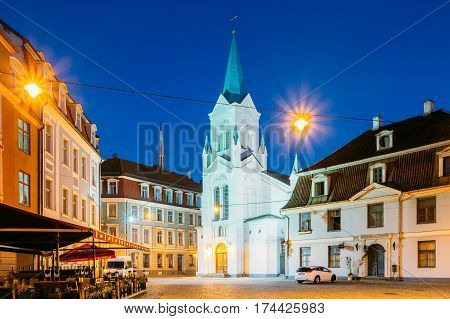 Riga, Latvia - July 1, 2016: Virgin Of Anguish Or Our Lady Of Sorrows Church, Ancient Catholic Church On Pils Street In Evening Illumination In Summer Among Original Architecture Of Old Town, Blue Sky