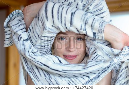 Pretty young woman undressing pulling a knitted cardigan or sweater over her head with her arms encircling her face