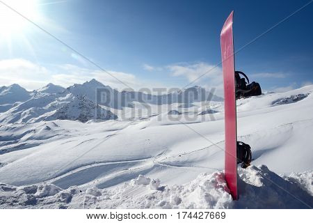 Snowboard in the snow on background ski slopes and snowy mountains