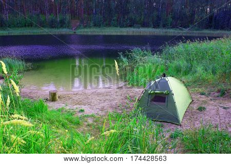 Tents in the forest in front of mountain lake