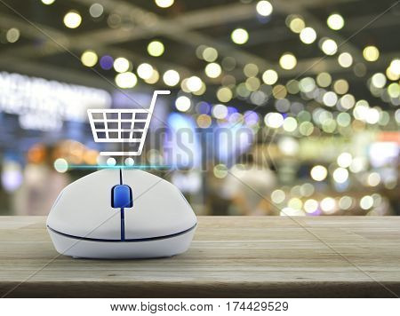 Shopping basket icon with wireless computer mouse on wooden table over blur light and shadow of shopping mall Shop online concept
