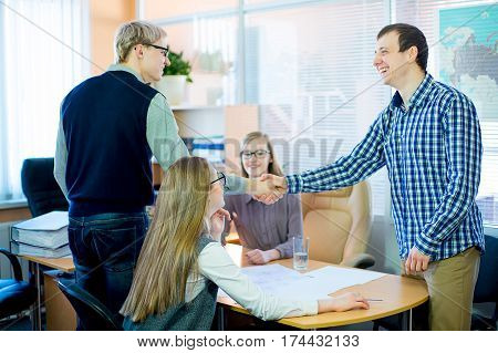 business team discussing at a table in an office, new business ideas. Two young men and two girls with glasses. two businessmen shaking hands