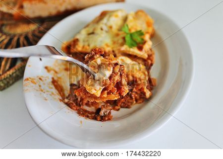 lasagna with meat on a white plate