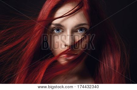 Sexy beautiful redhead girl with long hair. Perfect woman portrait on black background. Gorgeous hair and deep big blue eyes. Natural beauty clean skin facial care and hair. Strong and thick hair