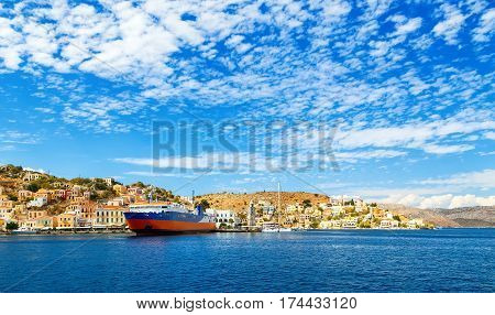 greek passenger sea ferry of Dodekanisos regular maritime traffic in bay of Simi island at the background of hills and blue sky