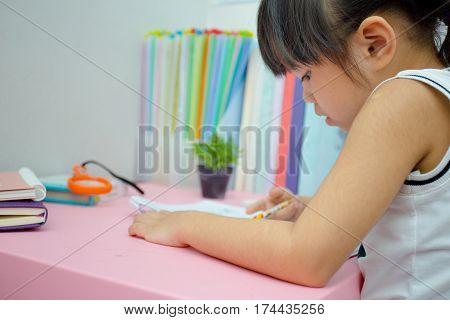 Little aisan girl is drawing with pen in preschool