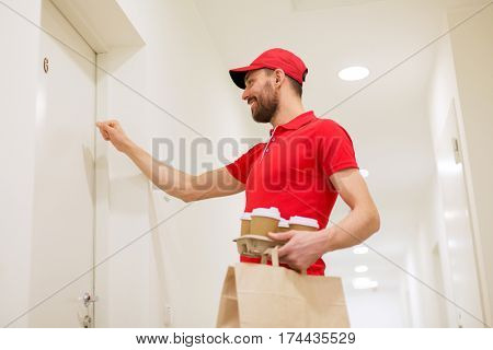 delivery, mail and people concept - happy man delivering coffee and food in disposable paper bag to customer home and knocking on door