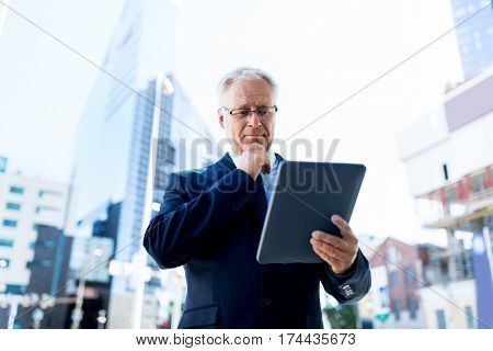 business, technology and people concept - senior businessman with tablet pc computer on city street