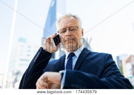 business, technology, time, punctuality and people concept - senior businessman calling on smartphone an looking at wristwatch or smart watch on his hand in city