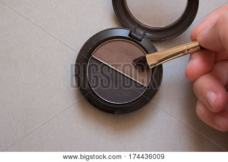 Brown and black shadows for brows brush and female hand on gray background
