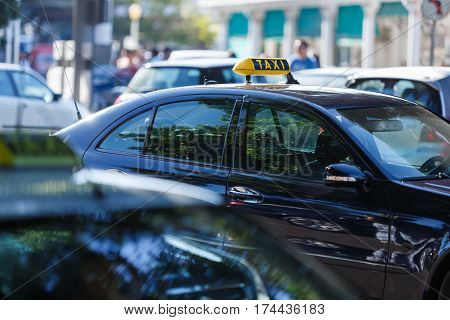 symbol or sign with an inscription of a taxi is located on a car roof on an indistinct background city street and blank space