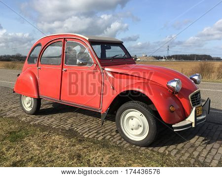 Almere, The Netherlands - February 21, 2017: Red Citroën 2CV (deux chevaux) parked by the side of the road in the city of Almere. Nobody in de vehicle.