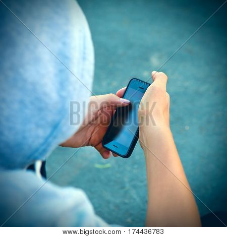 Vignetting Photo of Person with Cellphone sit on the City Street