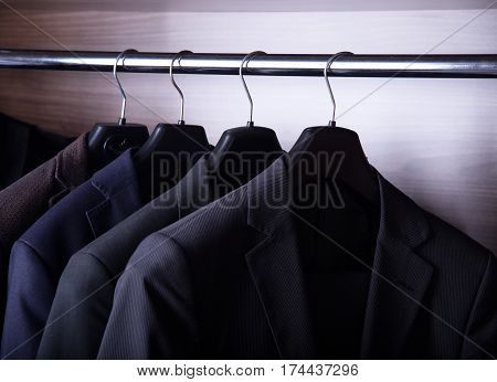 Men's suit jackets hanging in closet. Fashion suits