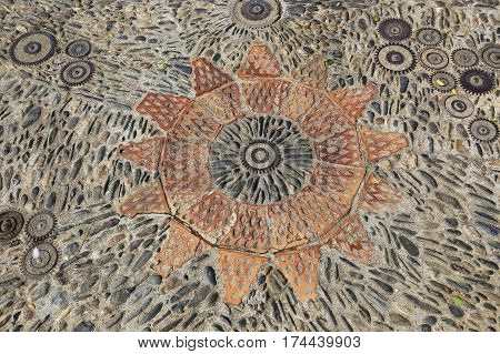 Patterned floor with pattern from pebbles bricks and gears in the park Montjuic Barcelona Catalonia Spain.