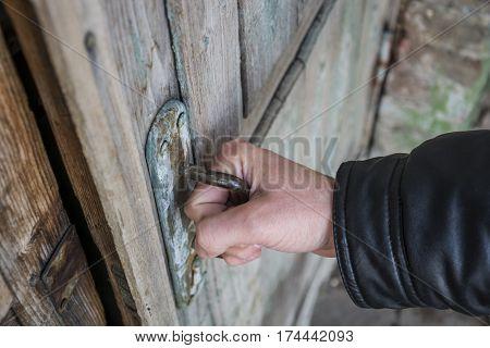 Wooden old door opens the man's hand