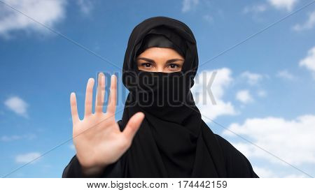 gesture, religious prohibition and people concept - muslim woman in hijab showing stop sign over blue sky and clouds background