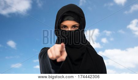 religious and people concept - muslim woman in hijab pointing finger to you over blue sky and clouds background