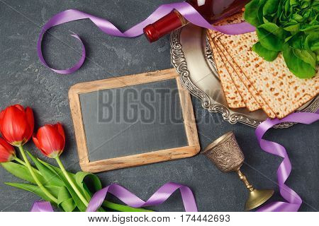 Passover holiday concept matzoh chalkboard and tulip flowers on dark background. Top view from above