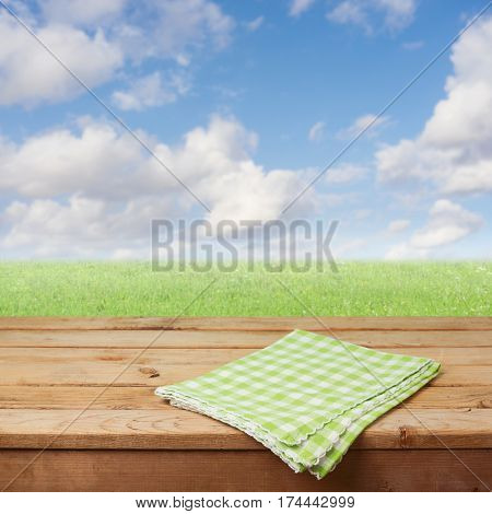 Empty wooden deck table with checked tablecloth over green grass meadow and blue sky background for product montage display