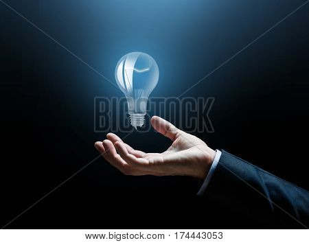 business, idea, inspiration and people concept - close up of businessman hand with light bulb over dark background