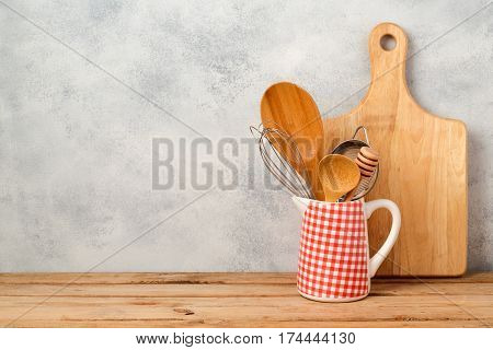 Kitchen utensils and cutting board on wooden table over rustic background