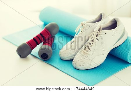 sport, fitness, healthy lifestyle and objects concept - close up of sneakers, dumbbells and sports mat