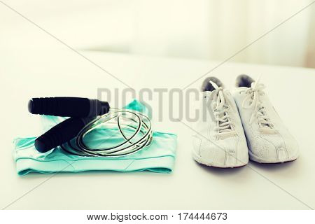 sport, fitness, healthy lifestyle, cardio training and objects concept - close up of sports top, sneakers and skipping rope on table