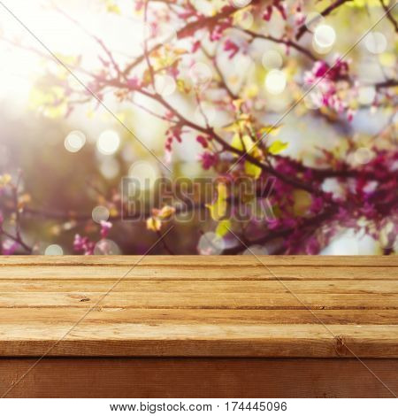 Empty wooden deck table over spring blossom tree background for product montage display