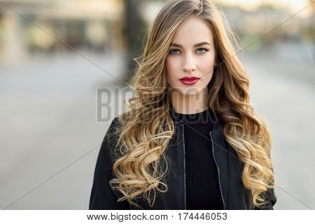 Young Blonde Girl With Beautiful Blue Eyes Wearing Black Jacket.
