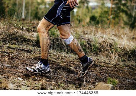 feet male runner runs dirty trail knee injury