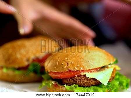 Hamburger fast food with ham on wooden board . Group of hamburger on blurred background. Piece of cheese hanging from sandwich. Human hand reaches for cheeseburger is not in field.
