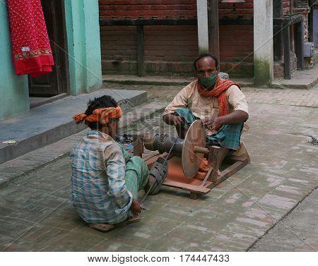 KATHMANDU, NEPAL. 23 September 2008: Urban residents in daily life. Grinders of knives on the street of old Kathmandu, Nepal.