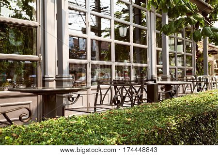 Empty outdoor cafe - metal forged furniture fenced by green hedge. Tables and chairs at restaurant terrace