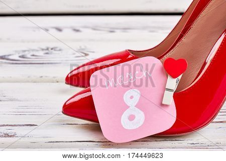 Female shoes on wooden backdrop. Elegant present for 8th March.