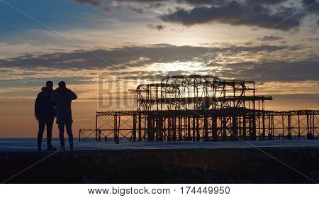 BRIGHTON GREAT BRITAIN - FEB 24 2017: Brighton west pier in warm evening light silhouette of two people watching the construction. Pebbles in the foreground. February 24 2017 in Brighton Great Britain