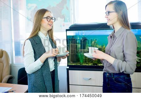 two girls gossiping over a cup of tea in the office on the background of the aquarium with fish