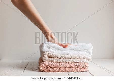 Towels preserved softness after washing. Woman's hand press the towel stack