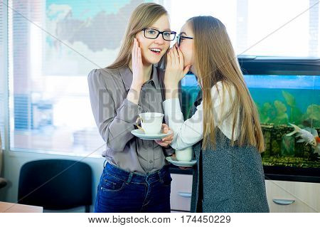 two girls gossiping over a cup of tea in the office on the background of the aquarium with fish. One girl whispers in the ear of the other