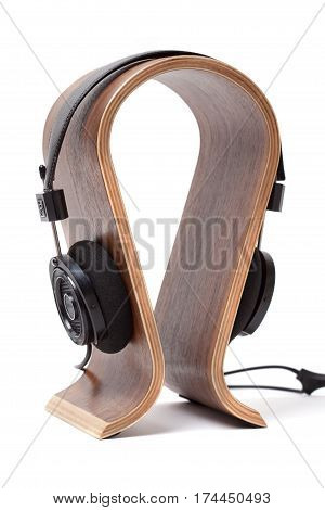 Black Pair of Headphones on a wooden stand Isolated on a White Background