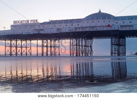 Brighton pier at sunset warm red colors. The pier reflecting in the water