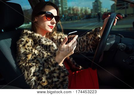 Beautiful woman in a fur coat with red lips using smartphone while driving