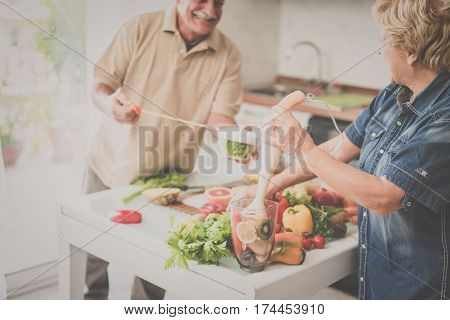 Senior couple cooking healthy vegan meal with fruits and vegetables together - Old happy people taking care about diet and health - Vegetarian and bio concept - Focus on woman hand - Matte filter