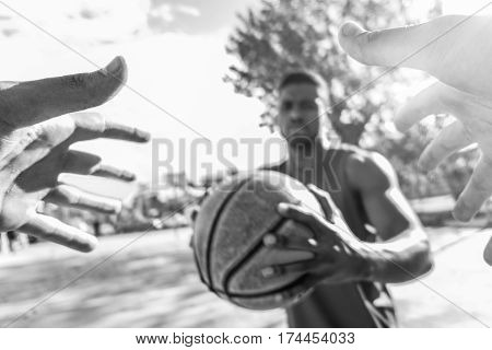 Multiracial basket players challenging in one to one game in urban court outdoor with back lighting - Athlete opposing to his african opponent - Focus on hands without ball - Black and white editing