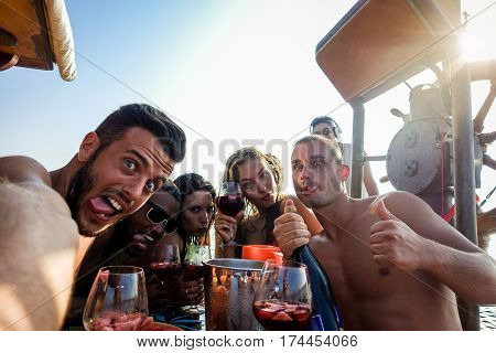 Happy friends taking selfie photo with mobile phone camera in boat party - Young people having fun in ibiza drinking champagne sangria - Summer vacation concept - Focus on right man - Warm filter