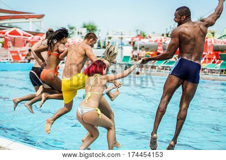 Young people looking happy while jumping into the swimming pool together - Happy friends having summer vacation party in aqua park - Holidays and youth concept - Focus on two right guys - Warm filter