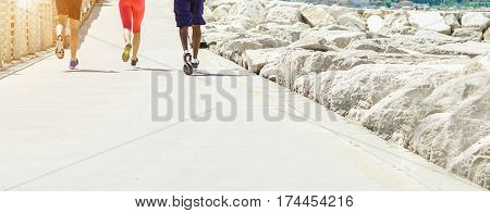 Young athletes training on beach running path lane - Athletic joggers running and speeding outdoor with sunset back light - Healthy lifestyle and sport concept - Warm filter with focus on center feet